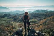 Vrouw kijkt in de diepte van het gebergte van Rec, Shkoder, Albanie.