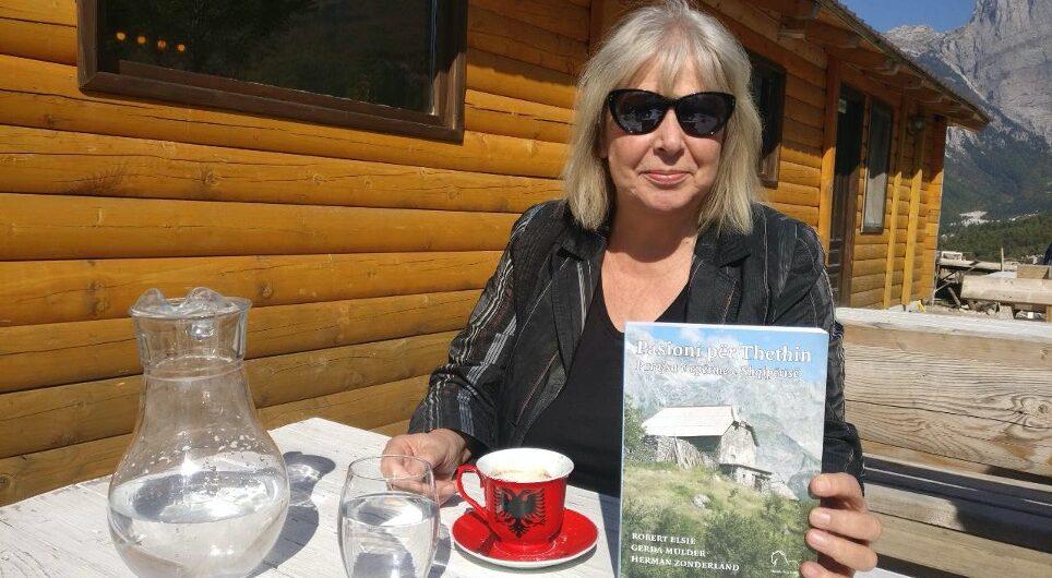 Gerda Mulder in Theth, drinkt koffie en laat het boek Passie voor Theth zien.