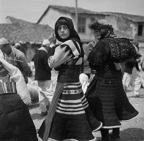 Twee vrouwen op een markt die xhubleta's dragen.